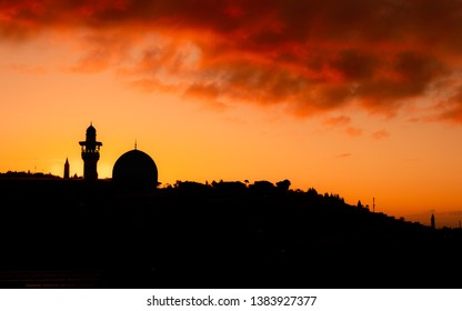 The Al Aqsa Mosque in Jerusalem silhoetted against a red sky at sunrise. This is the third holiest site in Islam.