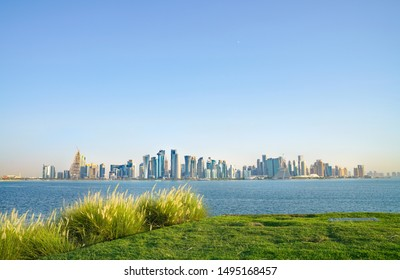 Al Dafna or Doha business district commercial skyline across Doha harbor from green grassy area near the Corniche on Old Town side.