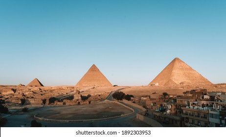 Al Haram, Giza Governorate, Egypt ; 02 08 2020: In the morning when the sun crosses the Giza pyramid complex. A time without people.