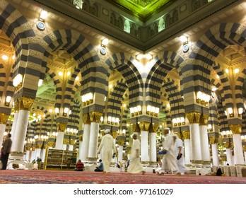 AL MADINAH, KINGDOM OF SAUDI ARABIA-FEB. 19: Muslim men walk on inside Masjid (mosque) Nabawi on February 19, 2012 in Al Madinah, S. Arabia. Nabawi mosque is the 2nd holiest mosque in Islam.