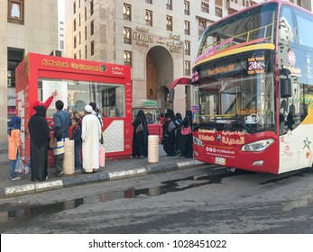AL MADINAH, SAUDI ARABIA-JANUARY 18, 2018:  Unidentified people queue to buy bus ticket at a hop on hop off bus counter outside Nabawi Mosque in Medina Saudi Arabia.