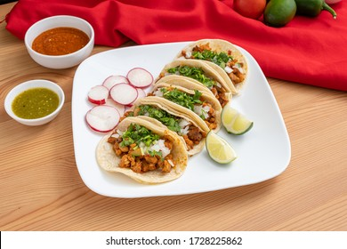Al pastor street tacos served in an authentic Mexican restaurant. Spicy pork tacos topped with cilantro and onion served on corn tortillas.