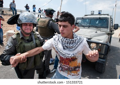 AL WALAJA, PALESTINIAN TERRITORY - MAY 10: Israeli soldiers arrest a Palestinian youth during a demonstration against the Israeli separation wall in the West Bank town of Al-Walaja, May 10, 2013.