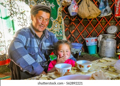 Ala Archa, Kyrgyzstan - circa September 2011: Smiling native man poses with his smiling daughter during breakfast in Ala Archa, Kyrgyzstan. Documentary editorial.