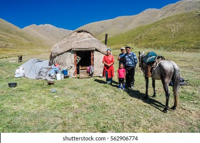 Ala Archa, Kyrgyzstan - circa September 2011: Smiling native family poses with their horse in front of their nomad tent in beautiful countryside of Ala Archa, Kyrgyzstan. Documentary editorial.