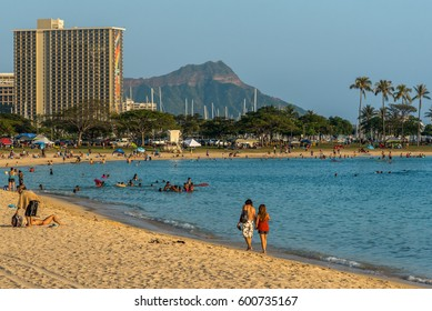 Ala Moana Beach Park, Hawaii - March 12, 2017: locals and tourists enjoy watersports and  walks along the beach at the ala moana beach park, near waikiki and the ala moana shopping center