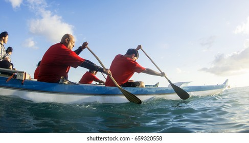 ALA MOANA BEACH PARK, HONOLULU, HAWAII - MAY 29, 2017: People paddle outrigger canoes out to sea to float religious ceremonial lanterns in a celebration to honor deceased loved ones.