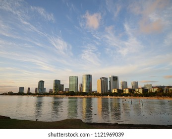 Ala Moana beach park street skyline buildings during golden hour warm yellow light Honolulu Hawaii Oahu island