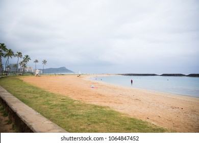 ALA MOANA, HAWAII - FEBRUARY 25, 2018: Ala Moana Beach and Magic Island Lagoon on a slow day because of overcast, cloudy conditions.
