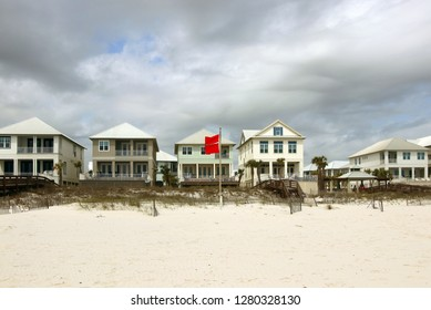 Alabama Gulf of Mexico beach life. Cloudy sky over the oceanfront houses for vacation rental and extremely dangerous warning sing with two red flags in a foreground.