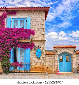Alacati, Cesme / Turkey - June 22 2017 : Colourful houses with flowers