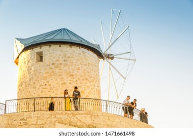 ALACATI,IZMIR / TURKEY, JULY 28, 2019: People enjoying the view of Alacati at the sightseeing terraces near the traditional wind mills. Alacati is a small touristic town at Cesme province of Izmir.