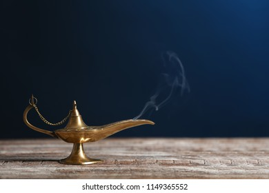 Aladdin lamp of wishes on wooden table against dark background
