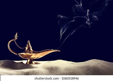 Aladdin magic lamp on sand against black background