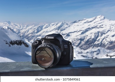 Alagna, Italy - April 22, 2018: close up on a Canon EOS DSLR, resting on a table top; in the background, snowy Alps are visible in full sunlight.