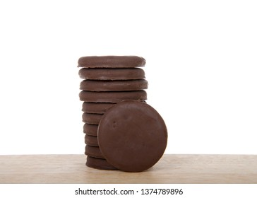 Alameda, CA - April 19, 2019: Stack of Girl Scout cookies, Thin mints, on a wood table with white background. Available annually during Girl Scout cookie sales.