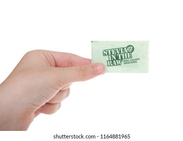 Alameda, CA - August 24, 2018: Young female hand holding package of Stevia in the Raw, a  zero-calorie sweetener. An extract from the sweet leaves of the stevia plant. Isolated on a white background.