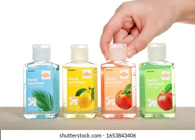 Alameda, CA - Feb 20, 2020: hand reaching in to pick up bottle of hand sanitizer from row of various scents on light wood table, isolated on white background. Travel size bottles.