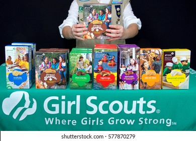 Alameda, CA - February 12, 2017: Traditional Girl Scout cookie booth with Little Brownie Baker brand cookies with a black background. Cadette Girl Scout holding up box of newest brand S'more cookies.