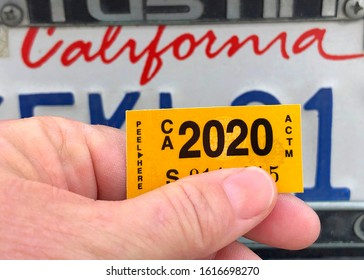 Alameda, CA - Jan 14, 2020: Close up of hand holding California DMV tags with CA license plate in background. Department of Motor Vehicle registration must be renewed annually.