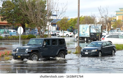 Alameda, CA - Jan 16, 2020: Vehicles drive through flooded road despite flood warning signs. It is recommended not to stop in the middle of flooded road to prevent water damage and stalling of vehicle
