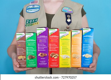 Alameda, CA - October 04, 2017: Cadette Girl Scout holding boxes of Girl Scout cookies. Girl Scout cookie sales help girls learn marketing and money management skills.