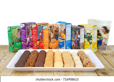 Alameda, CA - September 16, 2017: White tray with 8 varieties of Girl Scout Cookies on a wood table, boxes standing behind plate. Available annually during Girl Scout cookie sales from ABC Bakers