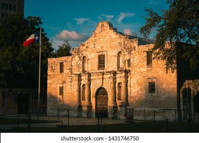 The Alamo at sunrise with the Texas Flag. Golden Light on The Alamo in San Antonio, Texas in the morning. Historical landmark.