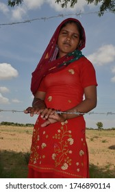 alana, Bikaner, Rajasthan / India - September 01,2012: Beautiful Rajasthani young girl standing in her farm in traditional Rajasthani dress