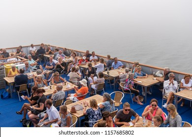 ALAND, FINLAND - JULY 31, 2018: Top view of many people sitting on deck outdoors at at cruise ship in Aland Finland july 31, 2018. Thick mist and fog in the background.