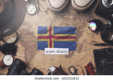 Aland Islands Flag Between Traveler's Accessories on Old Vintage Map. Overhead Shot