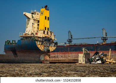 Alang ,Bhavnagar ,01, February, 2016:,    View showing  dismantled parts lying near half cut ship with background at Alang Ship Breaking Yard , Bhavnagar, Gujarat, India , Asia