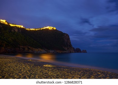 Alanya Castle (Alanya Kalesi) in night time under cloudy sky. View on sea from sandy Cleopatra Beach, Alanya, Turkey.