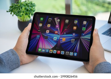 Alanya, Turkey - May 11, 2021: Man hand holding iPad Air IOS 14 with widget on the home screen. iPad was created and developed by the Apple inc.