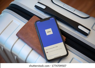 Alanya, Turkey - May 23, 2020: Luggage Delsey and iPhone 11 with application Taxi Uber on the screen.