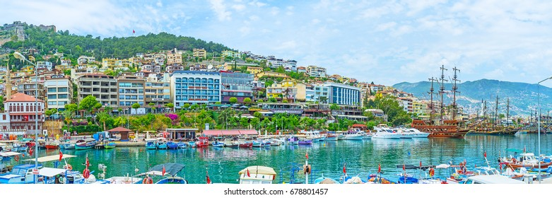 ALANYA, TURKEY - MAY 9, 2017: Panorama of fishing port with numerous motor boats, wooden tourist ships, row of modern hotels on the shore and Castle Hill on background, on May 9 in Alanya, Turkey.