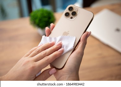 Alanya, Turkey - November 26, 2020: Woman hand holding Apple iPhone 12 Pro Max Gold and rubs it with rag. iPhone was created and developed by the Apple inc.