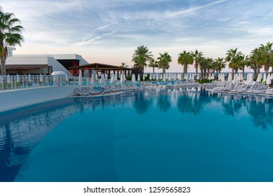 Alanya, Turkey - October 05, 2018. Beautiful pool in Kirman Sidera Luxury hotel with clear blue water on background of sea, blue sky and green palm trees. Beach chaise longue, summer vacation, tourism