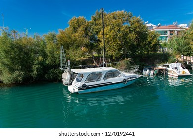 Alanya, Turkey - October 05, 2018. A small speedboat moored at the pier along the coast against a blue sky. Photos of the ship from the sea. The concept of summer holidays, sports, tourism