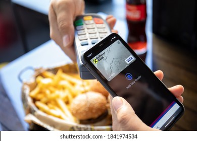 Alanya, Turkey - October 13 2020 : Man hand holding iPhone 11 with Apple Pay on the screen and pay pass online terminal the burger.