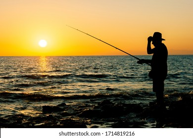 Alanya, Turkey, October 2019: Silhouette of a fisherman fishing in sunset time on the open sea.
