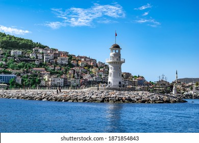 Alanya, Turkey - October 22, 2020: Panorama of Alanya with a white old lighthouse on the background of modern cottages on a mountainside. Beautiful cityscape and seascape in summer-autumn sunny day