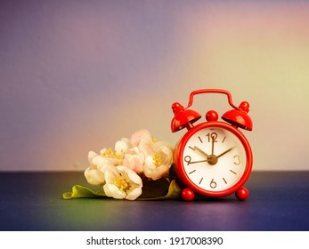 Alarm clock and beautiful spring flowers on blue table, space for text. Time change concept.
