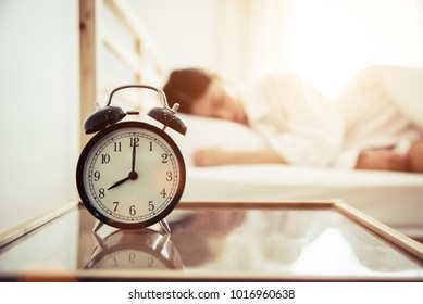 Alarm clock with beauty woman in background. Morning and Lazy time concept. Bedroom theme.