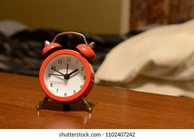 An alarm clock at the bedside table.