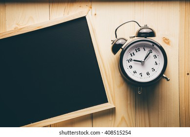 alarm clock and blackboard on wooden table.View from above and Vintage retouching.