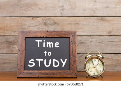 "Alarm clock and blackboard with text ""Time to study"""" on brown wooden background"