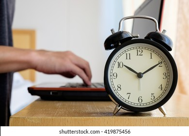 Alarm clock with blurred background of businessman work overtime until morning