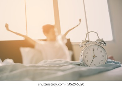 Alarm clock and blurry Teenage boy stretching hands after wakeup in bed, shallow depth of field focus on foreground.Cross processing and Split tone instragram like process.with Sun light.