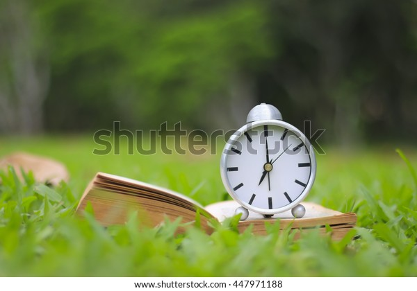 alarm clock and book with cup of coffee on the green grass